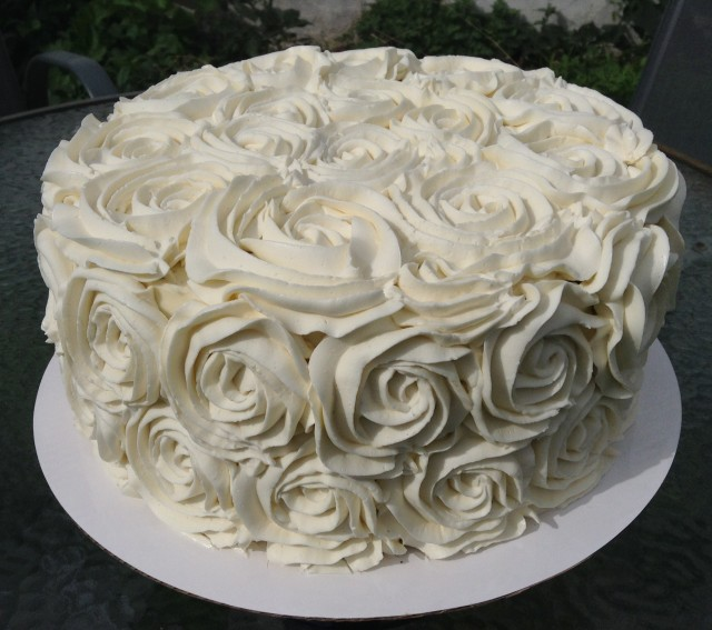 10 inch round cake covered in white rose swirls.